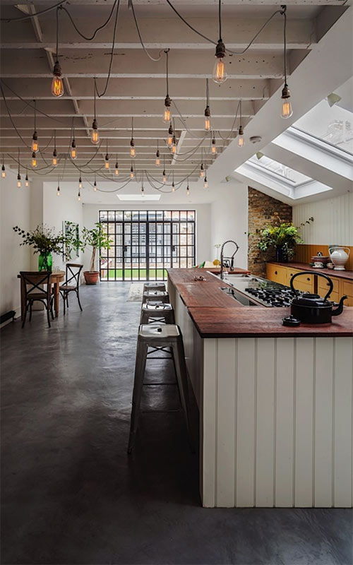 Image showing Edison bulbs lighting up a kitchen from a blog post by forthefloorandmore.com about summer decor inspo and how to bring the outdoors in.