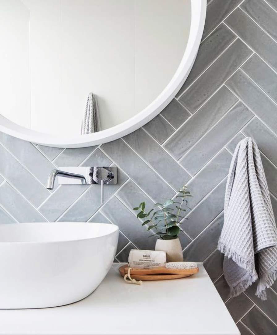 Image of a bespoke bathroom double herringbone metro tiles used in a blog post about herringbone flooring from forthefloorandmore.com