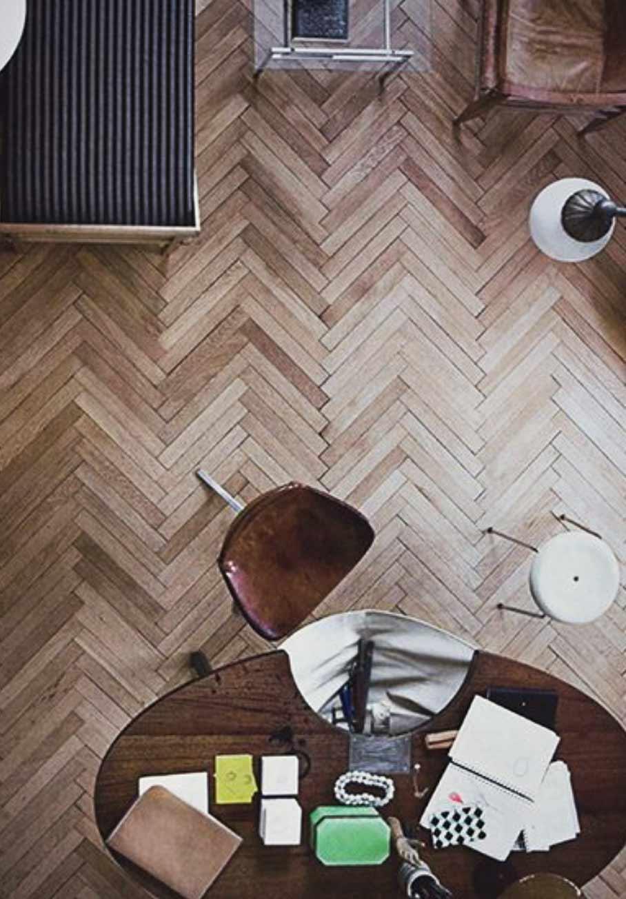Image of a hardwood herringbone lounge flooring installation used in a blog post by forthefloorandmore.com